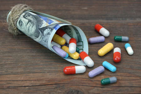 paid medicine: Tied With Rope Hundred Dollar Bill With Many Multicolored Pills Scatered On Rough Wood Table Background, Close Up, Front View Stock Photo