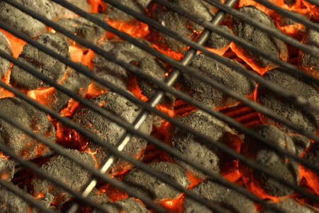 metal grate: BBQ Grill And Glowing Hot Charcoal Briquettes In The Background, Close-Up, Top View. Concept For Outdoor Barbecue Party Or Picnic Or Cookout