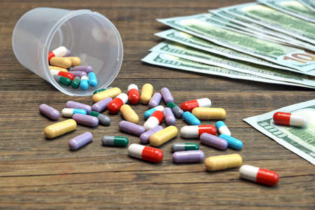 hospital fees: Dollar Cash And Scattered Pills On The Rough Wood Background, Top View, Conceptual Image