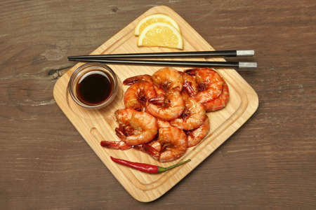 king size: Grilled Red King Size Shrimps Or Prawns With Sauce, Chili Pepper and Lemon, Served With Wood Chopsticks On Wood Board  Isolated On Wooden Background, Close Up, Top View