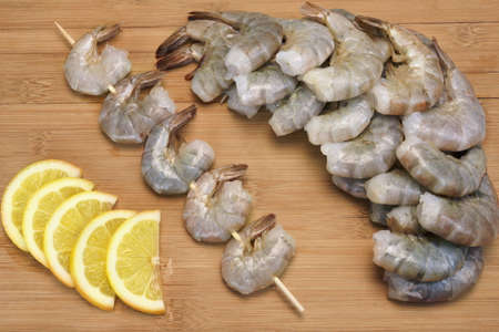 king size: Many Raw Green King Size Shrimps or Prawns On Wooden Skewers With Yellow Lemon Slices On Wooden Background