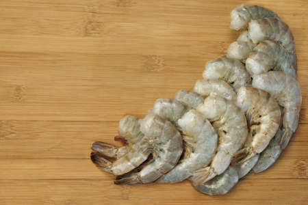 king size: Many Raw Green King Size Shrimps or Prawns On Wooden Board Background, Top View, Close Up, Isolated Stock Photo