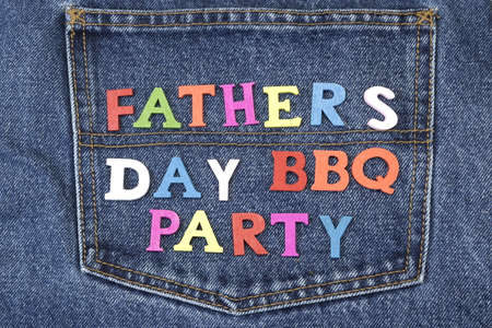 felicitation: Colorful Wooden Father's Day BBQ Party Sign On The Blue Jeans Back Pocket, Close Up