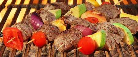 kebob: Barbecue Spit Roasted Beef Kebabs On The Hot Grill Close-up. Flames of Fire In The Background Stock Photo
