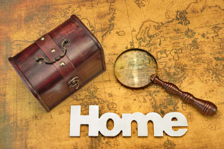 storage box: Home Search Or Emigration Concept. Bag Or Storage Box, Wooden Sign Home And Magnifier On the Old Map Background, Top View, Close Up Stock Photo