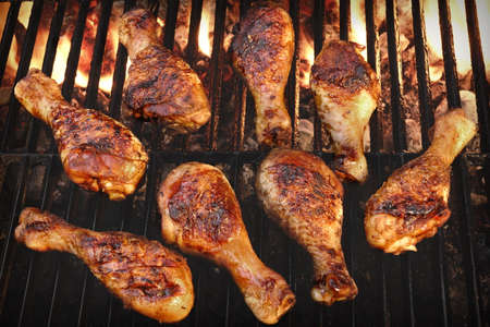 at close quarters: BBQ Grilled Chicken Legs On The Hot Flaming Grill, Top View. Cookout Food, Good Snack For Outdoor Party Or Picnic Stock Photo