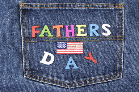 felicitation: USA Flag Label And Colorful Wooden  Father�s Day Sign On The Blue Jeans Back Pocket Background, Close Up