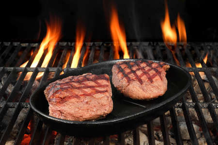 browned: Two Browned Strip Beef Steaks In The Cast Iron Frying Pan On The Hot BBQ Charcoal Grill With Bright Flames On The Black Isolated Background, Top View, Close-Up