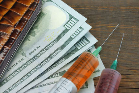 predilection: Wallet With US Dollar Cash And Two Syringe On Grunge Wood Background, Close Up Stock Photo