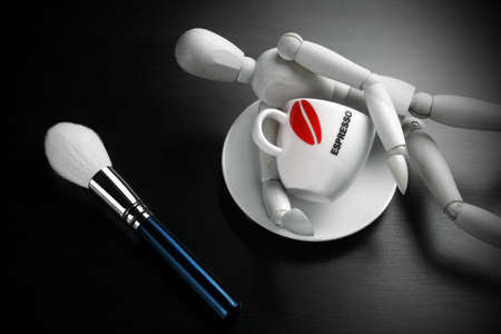 wood figurine: Empty Coffee Cup, Makeup Powder Brush and Wooden Mans Figurine On Black Wood Background, Close-up, Concept For Beauty, Dating, Flirting Top View
