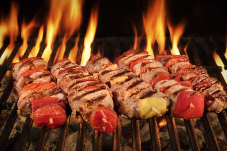 Many Shish Kebab From Different Meat With Pepper And Tomato On The Hot Charcoal BBQ Grill With Bright Flames On The Black Background, Cookout Concept, Close Up, Top View