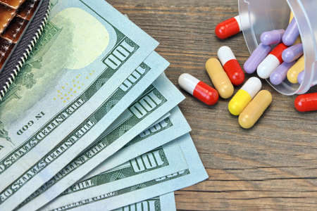 hospital expenses: Wallet With US Dollar Cash And Scattered Pills On The Rough Wood Background, Top View, Conceptual Image