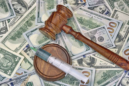bail: Wood Judges Gavel And Medical Syringe With Injection On The Dollar Cash Background, Overhead View, Concept For Medical Negligence Or Doctor Mistake, Bail, Monetary Compensation