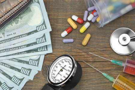 two us dollar: Wallet With US Dollar Cash,  Two Souring, Sscattered Pills And Doctor Tools On The Rough Wood Background, Top View, Conceptual Image