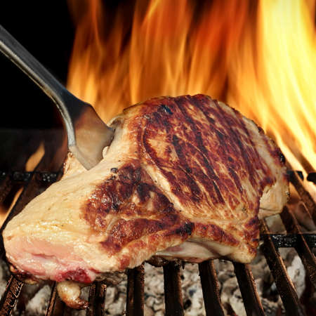 browned: Browned Pork Loin Steak On The Hot Barbecue Charcoal Grill With Fork, Bright Flames Of Fire On The Black Background, Close Up, Front  View, Cookout Food For Outdoor Party Or Picnic Stock Photo