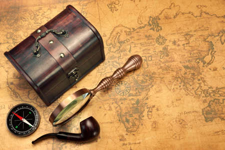 map case: Travel Still Life With Different Objects Case, Magnifier, Smoking Pipe and Compass On Old Brown Vintage Map Background
