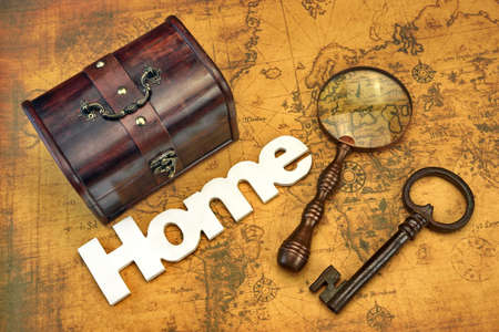 emigration: Home Search Or Emigration Concept. Bag Or Storage Box, Wooden Sign Home And Magnifier On the Old Map Background, Top View, Close Up Stock Photo