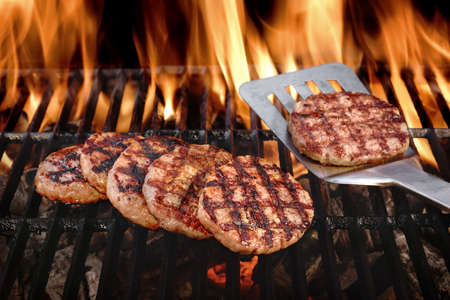 Beef Burgers And Spatula On The Hot Flaming BBQ Charcoal Grill, Close-up, Top View Banque d'images