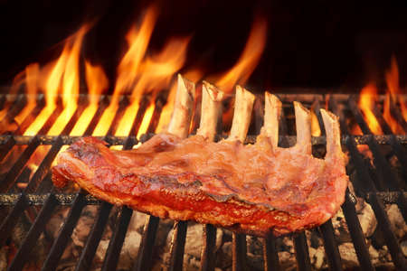 back rub: Marinated With BBQ Sauce Pork Spare Rib On The Hot Charcoal Grill With Bright Flames In The Background, Close Up Stock Photo