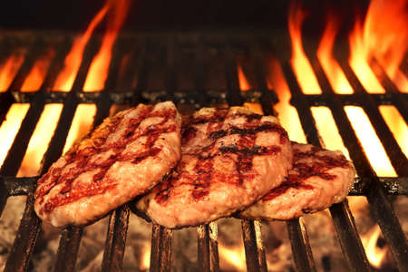 browned: Three Homemade Browned Burgers On The Hot Flaming BBQ Charcoal Grill, Bright Flames On The Black Background