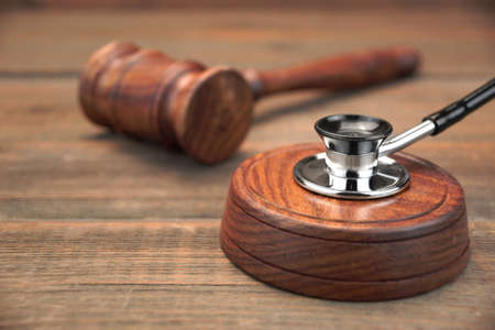 stetoscope: Doctors Stetoscope and Judges Gavel Laying On Brown Wooden Background, Medicine and Law Concept, Macro, Close-up, Front View
