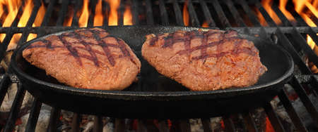 browned: Two Browned Strip Beef Steaks In The Cast Iron Frying Pan On The Hot BBQ Charcoal Grill With Bright Flames In The Background, Top View, Close-Up