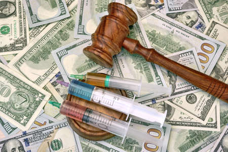 parole: Wood Judges Gavel And Medical Syringe With Injection On The Dollar Cash Background, Overhead View