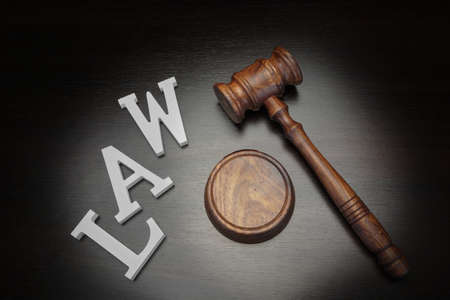 criminal case: Top View Of Judges Gavel And White Sign Law On The Black Wood Background, Conceptual Image