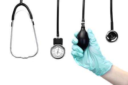 put pressure: Isolated Female Hand In Rubber Glove Holding A Doctor Equipment, Sphygmomanometer And Stethoscope Hang On The Wall