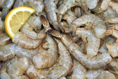 king size: Many Raw Green King Size Shrimps With Slices Of Yellow Lemon, Top View, Close Up, Isolated Stock Photo