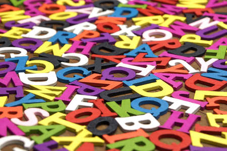 english letters: Random Chaotic Pattern From English Wooden Multicolored Letters On the Brown Wood Background Stock Photo