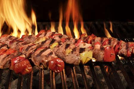 Muchos Shish Kebab de diferentes carne con pimienta y tomate en el Hot Charcoal Grill barbacoa con las llamas brillantes en el fondo Negro, Cookout concepto, de cerca, vista superior Foto de archivo - 55304604