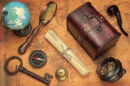 paper roll: Travel Concept Objects, Globe, Magnifier, Compass, Key, Bell, Paper Roll, Old Clock And Smoking Pipe On Old Vintage Map Background Stock Photo