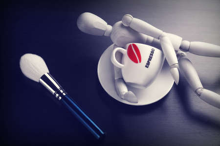 wood figurine: Empty Coffee Cup, Makeup Powder Brush and Wooden Mans Figurine On Black Wood Background, Close-up Stock Photo