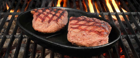 browned: Two Browned Strip Beef Steaks In The Cast Iron Frying Pan On The Hot BBQ Charcoal Grill With Bright Flames In The Background