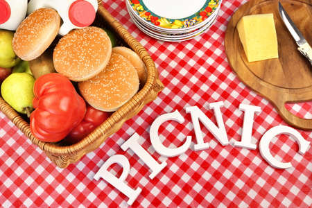 Sign Picnic Made From White Letters On The Table With  Red Checkered Tablecloth And Lunch In Basket, Top View