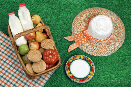 pic nic: Summer Picnic Concept With Straw Hat And Food Basket On The Fresh Green Lawn Background, Overhead View