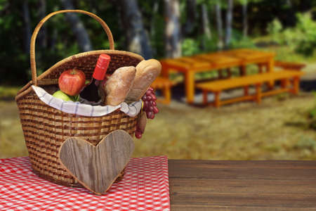 picnic food: Picnic Basket With Red Wine Bottle, Bread And Fruits On The Wood Table And Landscape With Picnic Bench And Summer Garden On The Blurred Background
