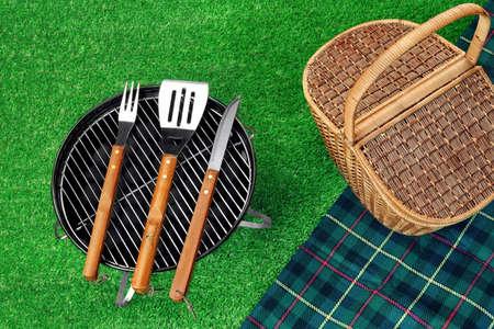 holzbriketts: Sommer-Picknick-Szene auf dem Gras. Tragbare Barbecue Grill mit Holzkohle-Briketts, Grill Tools Kit, Geschlossen Weidenkorb und Decke. Top View Lizenzfreie Bilder