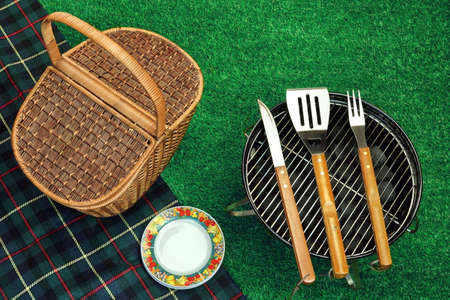 briquettes: Summer Picnic Scene On The Grass. Portable Barbecue Grill With Charcoal Briquettes, BBQ Tools Kit, Closed Wicker Basket And Blanket. Top View