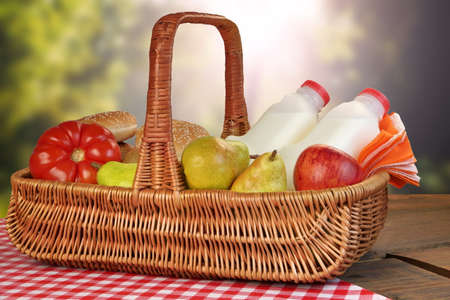 picnic food: Closeup Of Picnic Basket With Food And Drink On The Table With Red Checkered Tablecloth And Summer Rural Landscape With Sunlight In The Background Stock Photo