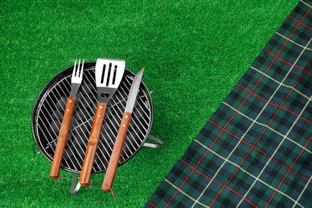 holzbriketts: Sommer-Picknick-Szene auf dem Rasen. Tragbare Barbecue Grill, Werkzeuge und Decke. Top View
