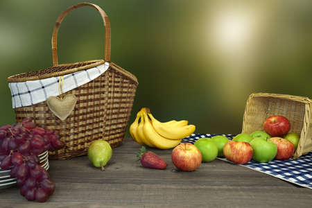 wooden basket: Closeup Of Picnic Basket With Fruits On The Table With Blue Checkered Tablecloth And Summer Garden In The Background Stock Photo