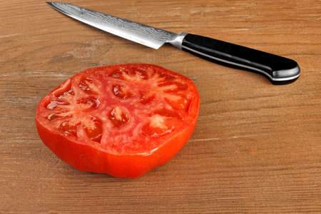 tomato slice: Ripe Sliced Red Large Tomato And Japanese Kitchen Knife On Wood Table Background, Closeup, Top View Stock Photo