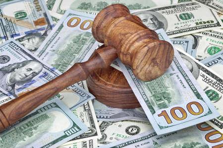 裁判官や競売の小槌やハンマー、木製テーブルの上のお金の巨大なヒープの試験では、オークションのための概念のための概念をクローズ アップ、