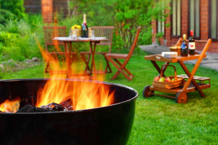 Fin de semana de verano Escena barbacoa en el patio trasero. Flaming Parrilla de carbón de primer plano. Muebles de madera al aire libre en el fondo borroso.