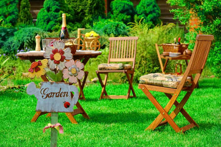 Wooden Plate In The Shape Of A Watering Can And Garden Sign. Outdoor Wooden Furniture On The Grass. Dinning Table With Food And Drink. Family Home Party Or Picnic Scene In Summertime Stock Photo