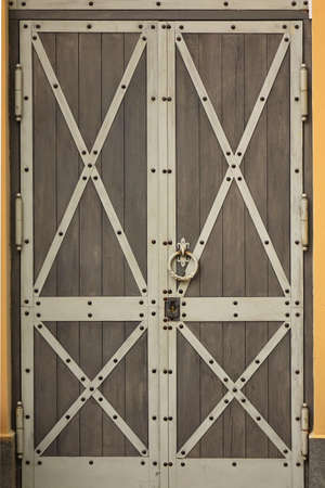 reinforced: Closeup Of Reinforced Double Leaf Wooden Door With Iron Element And Forged Ring Handle