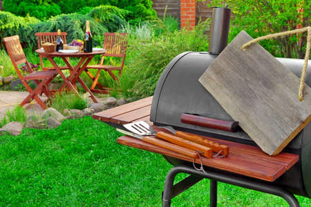 lawn party: Empty  Wooden Signboard Hanging On Barbecue Grill Appliance, Grilling Tools And Wooden Table With Food And  Beverages On The Backyard Lawn In The  Background, Summer Family Home Party Or Picnic Concept Stock Photo