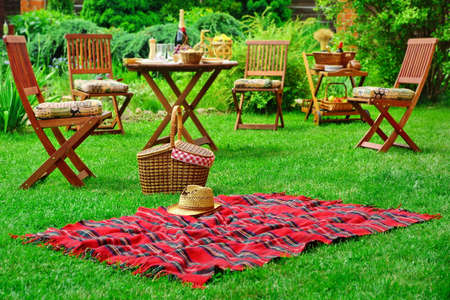staycation: Closeup Of Red Picnic Blanket With Straw Hat And Basket Or Hamper. Blurred Outdoor Wooden Furniture In The Background. Family Home Backyard Party Or Picnic Conceptual Scene Stock Photo
